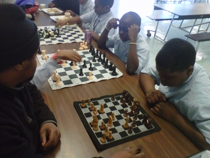 Pawnmaster David McDuffie and 6th grade students play chess during the lunch period